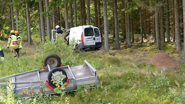 Bil och släp i skogsparti.