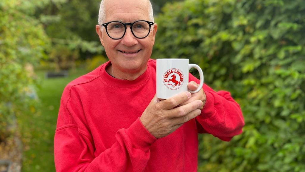 Nils-Inge Gustavsson visar en kopp med Trojas logotyp.