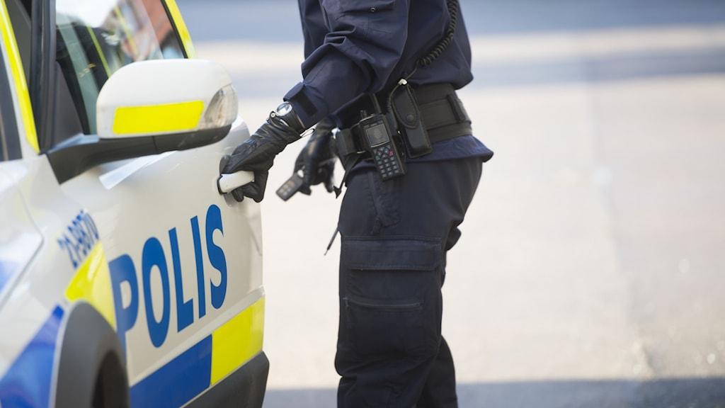 en polis går in i en polisbil
