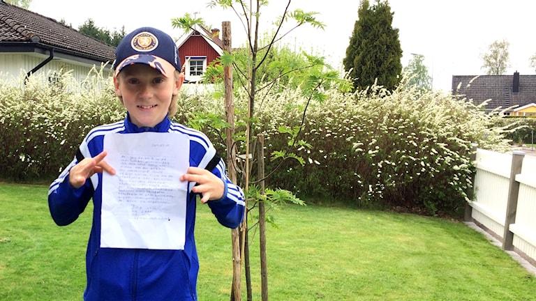 Oscar Olsson håller upp brevet som han skrev som 10-åring.