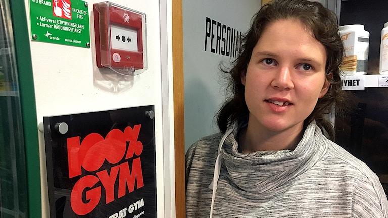 """Ninni Martinsson och en skylt med texten """"100% GYM"""""""