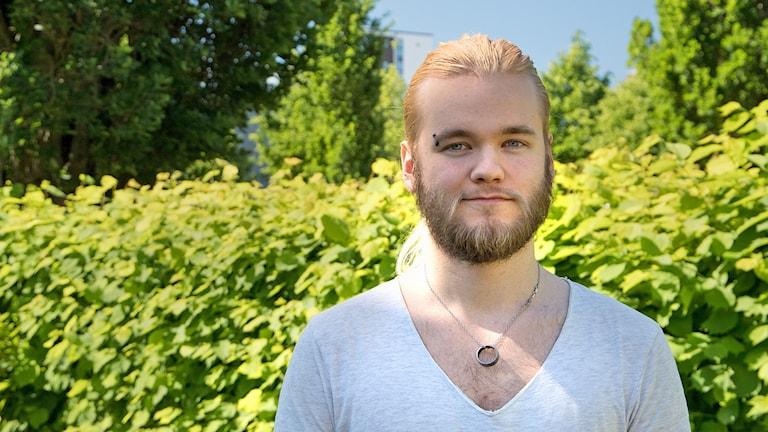 Rasmus Cinthio som tävlar i P4 Nästa står framför en grönskande häck.