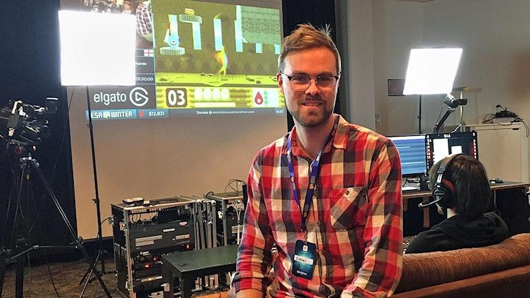 Fredrik Lidholt sitter framför en storbildsskärm när dataspelande pågår.
