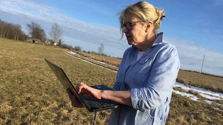 Stella Nilsson ute på en åker  med datorn för att få bättre internetuppkoppling.