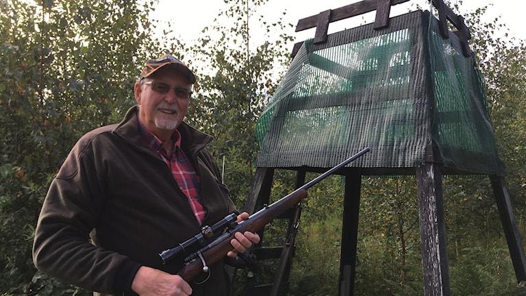 En man håller i ett gevär framför ett jakttorn.
