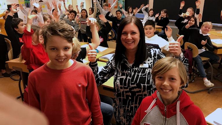 Hjortsbergskolan 5E med de tävlande leendes längst fram och klassen jublandes i bakgrunden.