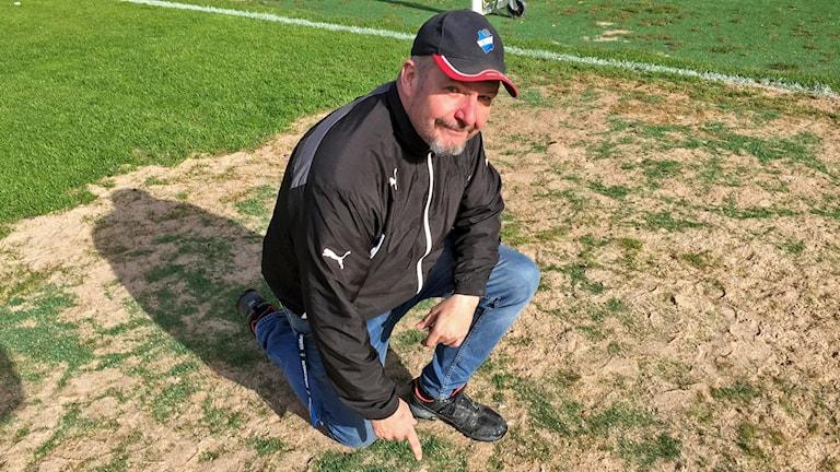 Ron Wähämäki, arenaansvarig på Myresjöhus Arena sitter på huk i målområdet som knappt har något gräs.