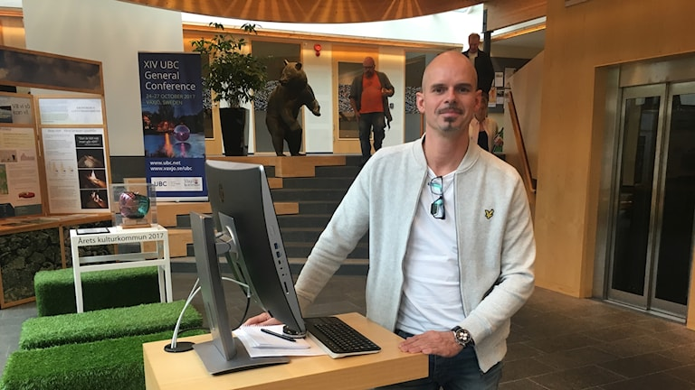 I bilden Peter Bergehamn som är it chef. Han har vit t-shird och en tröja öppen. Han står vid en dator med plattskärm som står uppställd i entrén i på Växjö kommun.