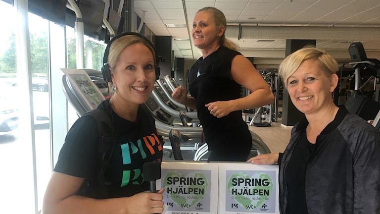 Tre kvinnor står vid ett löpband på ett gym