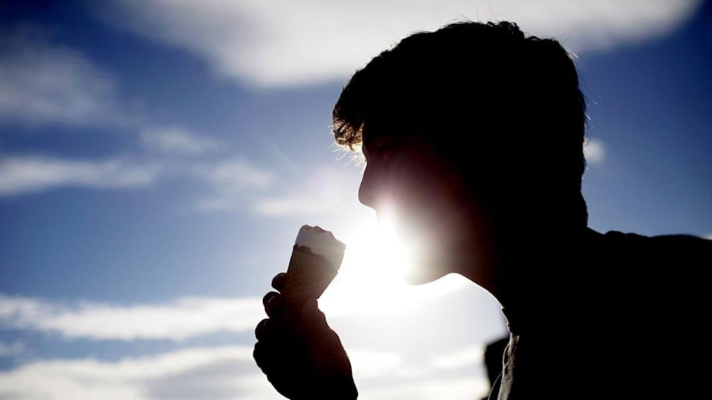 Person i motljus äter glass.
