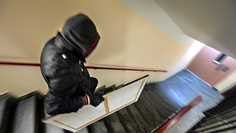 En tjuv med huva som springer i en trappa.