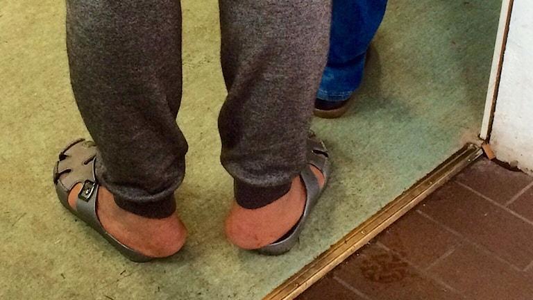 Fötter i sandaler på ett smutsigt golv