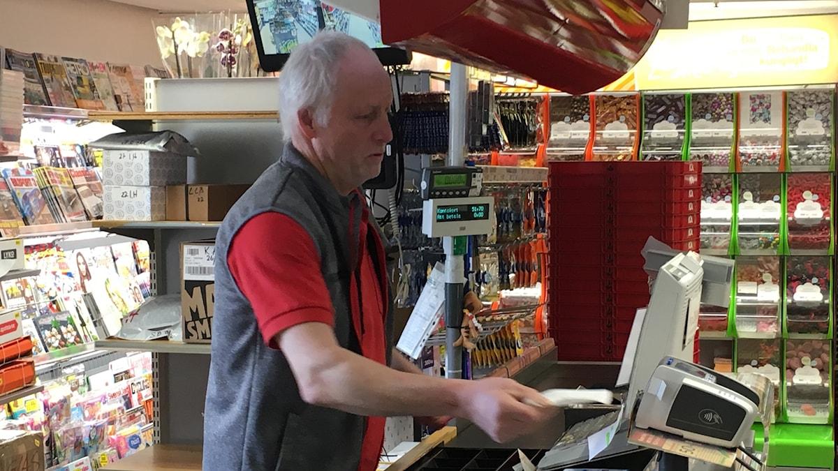 Leif Fransson lanthandlare i Grimslöv i bilden framför sin kassa i butiken.