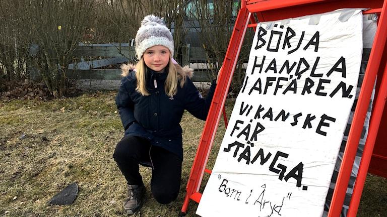 """Tioåriga Wilma Bertilsson håller upp skylten som hon gjort. Det står: Börja handla i affären. Vi kanske får stänga. """"Barn i Åryd"""""""