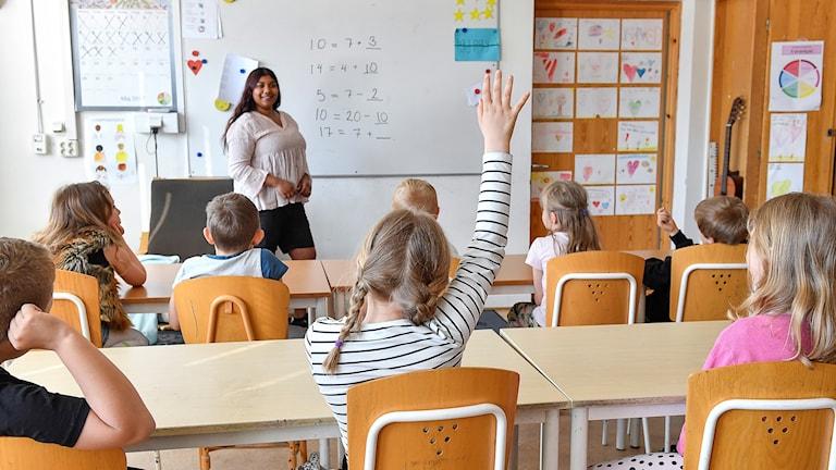 Flicka räcker upp handen i klassrum. Vid tavlan står läraren och har skrivit mattetal på tavlan.