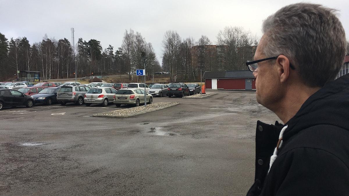 Rektorn tittar ut över den fulla parkeringen utan för skolan.