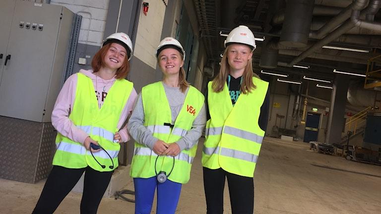 Iris Bernhardsson, Nellie Falkebrink och Alva Flykt står i reflexvästar och vita hjälmar i en maskinhall på Sandviksverket.