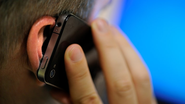 En man håller en mobil mot örat.