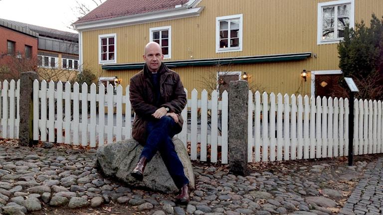 Fredrik Modéus, biskop, sitter på en sten framför ett hus.