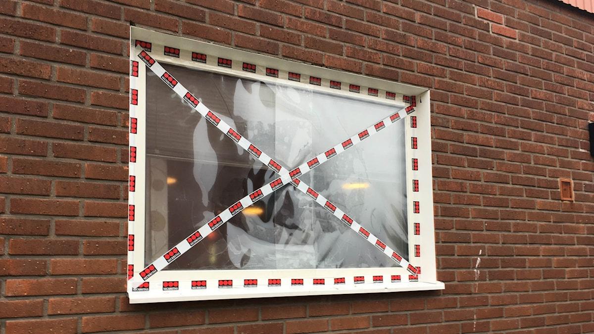 Ett krossat fönster har plast och röda plastremsor i ett kryss över sig.