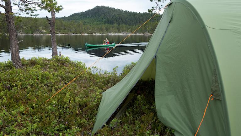 Ett tält står upprest. I bakgrunden syns en sjö med en kanotpaddlare.