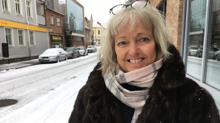 En kvinna med kappa på sig står vid en gata i Växjö. På marken ligger snö.