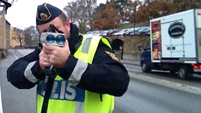 Polis som kollar hastigheten med laser.