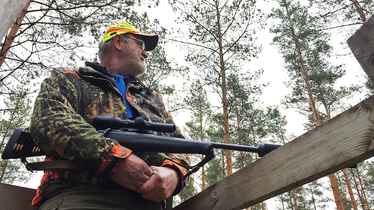 En jägare står med sitt gevär