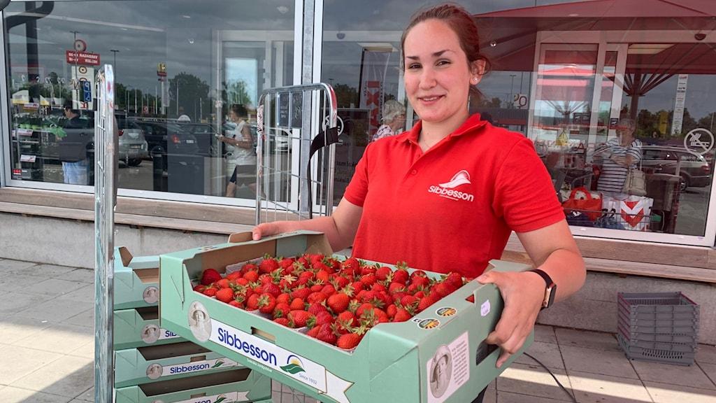En tjej står i röda kläder och håller upp jordgubbar.