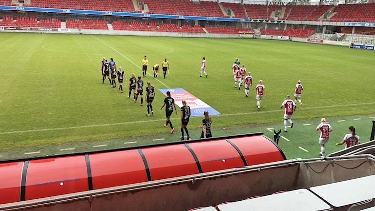 Fotbollsspelare går på en fotbollsplan.