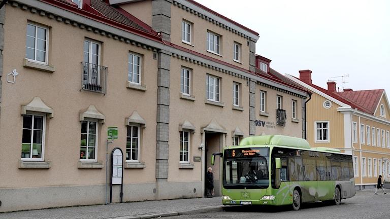 En grön buss utan för ett stort beiget hus