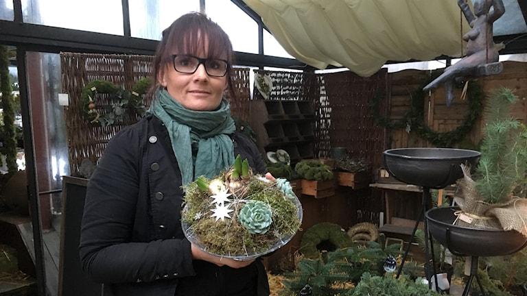En kvinna står i ett växthus och håller upp ett blomsterarrangemang på ett fat