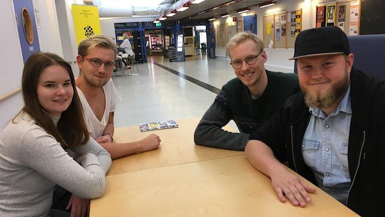 Fyra studenter sitter runt ett bord i en korridor på Linnéunviersiteet. De tittar in i kameran och ser glada ut.