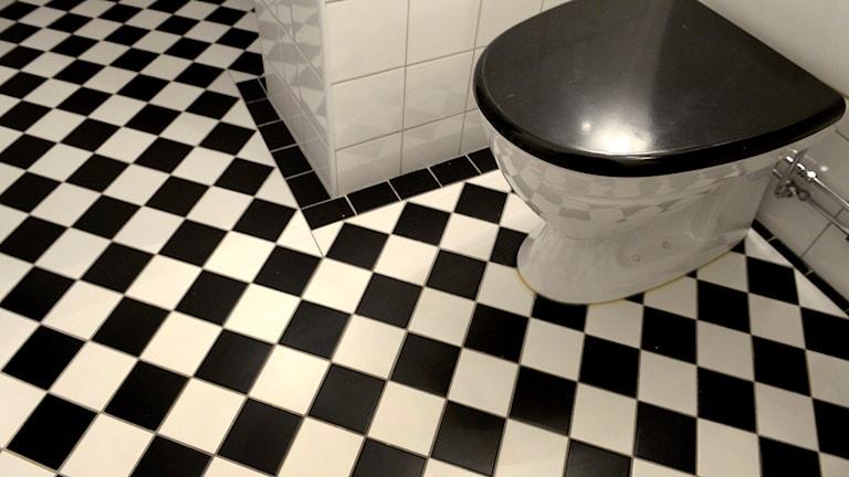 Toalett och svartvit-rutigt golv.