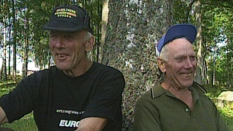 Bröderna Erik och Sigvard sitter framför ett träd.