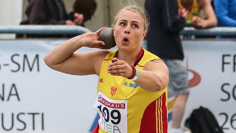 En kvinna i gult linne med nummerlapp håller en kula mot kinden med höger hand. Hon pekar rakt fram med vänsterarmen.
