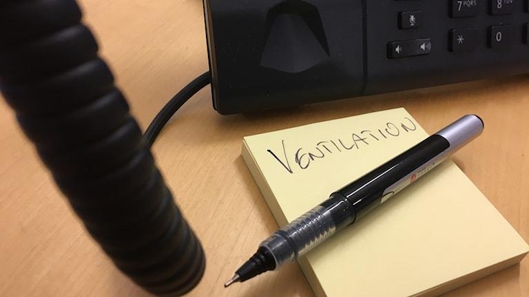 En telefon och en penna på ett postit-block.