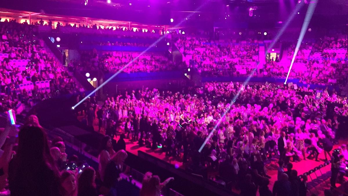 Vida arena uppyst med massa lila lampor och fullt med publik.