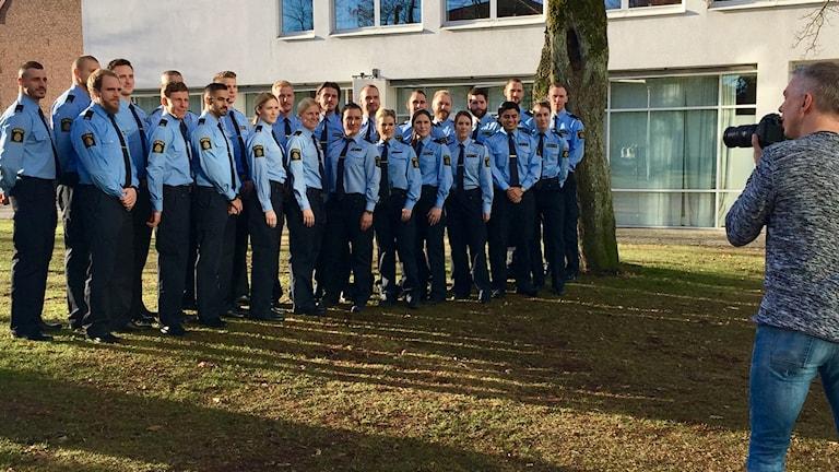 Polisstudenter tar examen och fotograferas i en gruppbild av en fotograf.