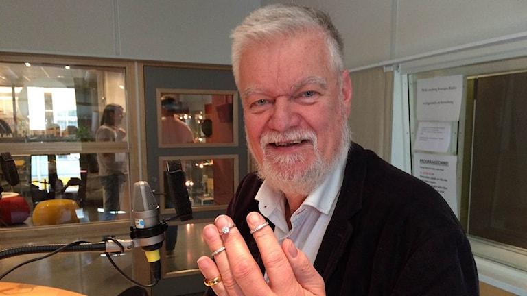 myckeshandlare Göran Magnusson har fyra stycken vigsel- förlovningaringar på sin hand vid mikrofonen i radiostudion.
