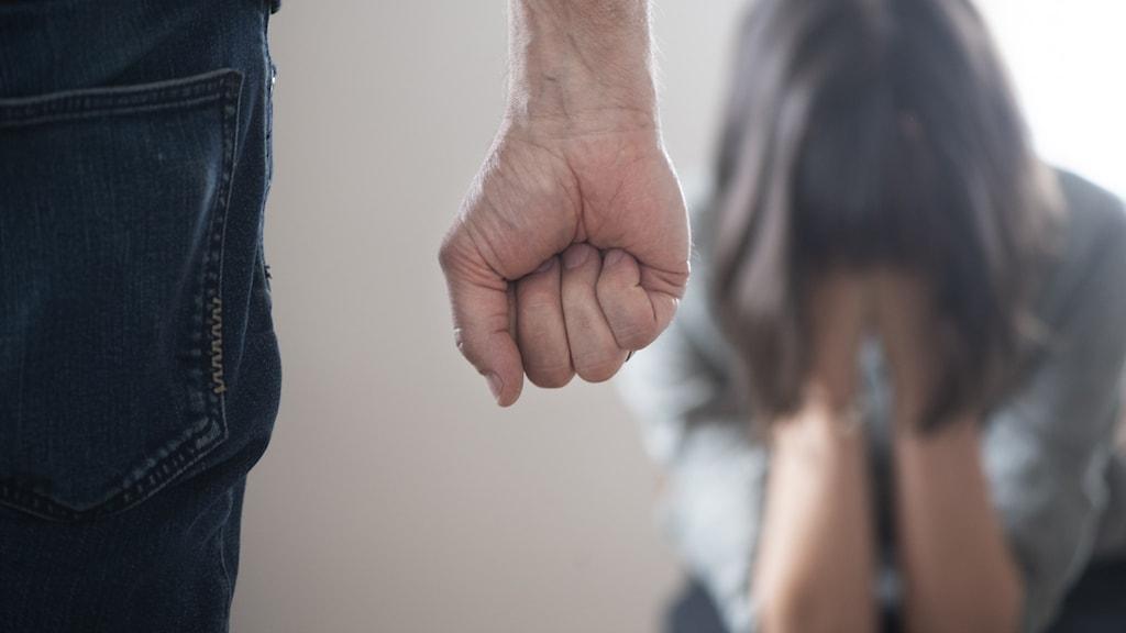 en hand som är knuten och kvinna som är ledsen.
