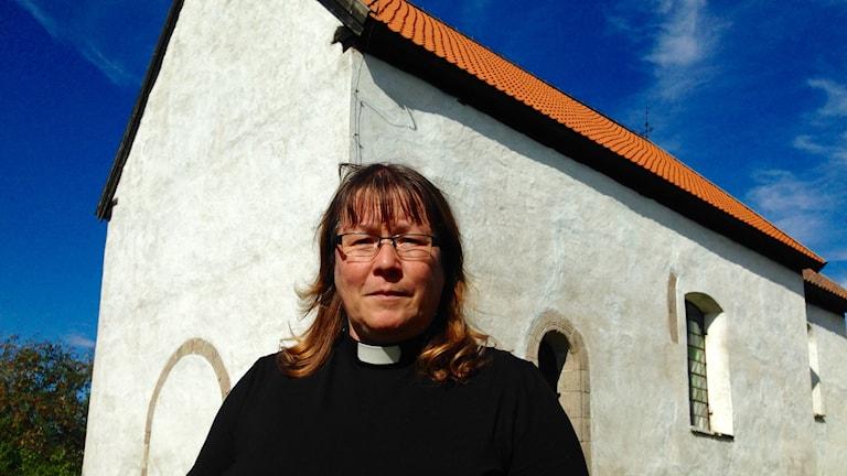 Prästen Ursula Björkman Sjögren står framför Hemmesjö gamla kyrka