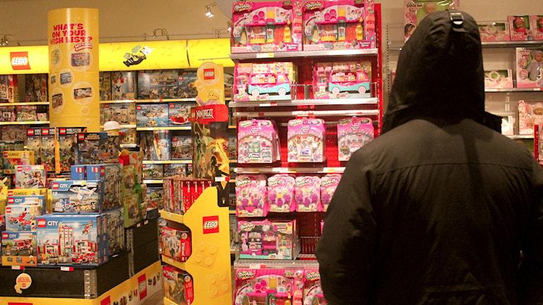 En person tittar på en vägg av leksaker.