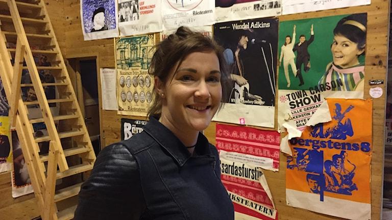Frida Sundqvist-Hall framför en vägg med affischer