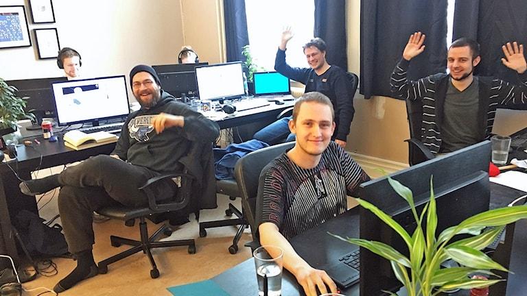 I bilden flera av de tyska spelutvecklarna i Fridafors vid sina datorer som vinkar mot kameran.