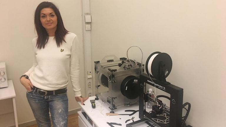 Aida i en vit tröja står vid en mekansik 3D utrustning. Hon stödjer sig med ena handen i bordet och tittar in i kameran.