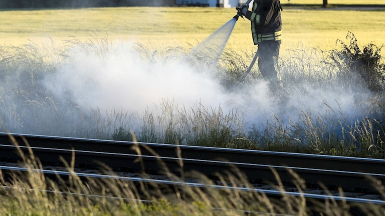 Brandman bekämpar gräsbrand vid tågräls.