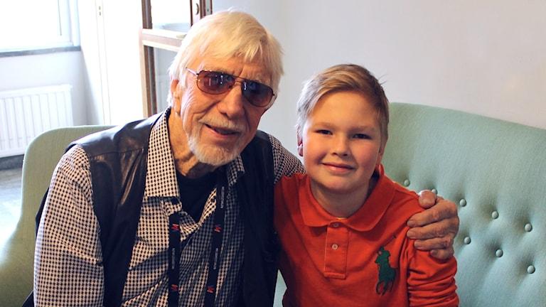 Owe Thörnqvist håller ena armen om 11-åriga Wille Helgé. De sitter i en grön soffa.