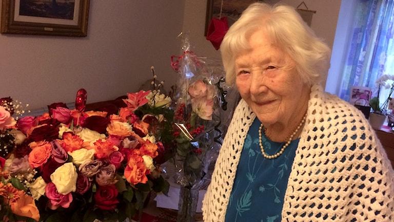 Edit Carlsson fyllde hundra år i dagarna. Står framför sina blommor.
