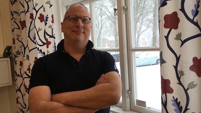 Per Gjörloff står framför ett fönster med blommiga gardiner